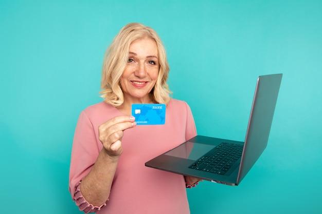 Frau, die internet für online-einkauf mit computer und kreditkarte verwendet.