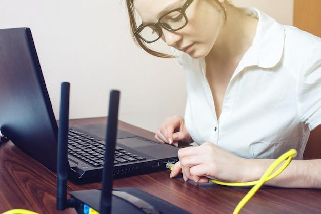 Frau, die internetkabel zum verbinder auf dem laptop verbindet