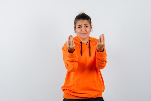 Frau, die italienische geste macht, mit dummer frage im orangefarbenen hoodie unzufrieden ist und hilflos aussieht