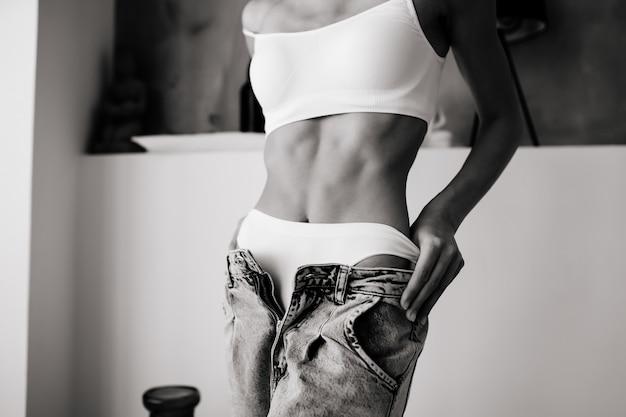 Frau, die jeans, weiße unterwäsche auszieht. junge frau zieht ihre jeans aus. frau sieht sinnlichkeit und sexy aus.