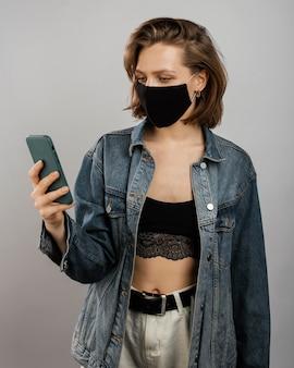 Frau, die jeansjacke und -maske beim verwenden des handys trägt