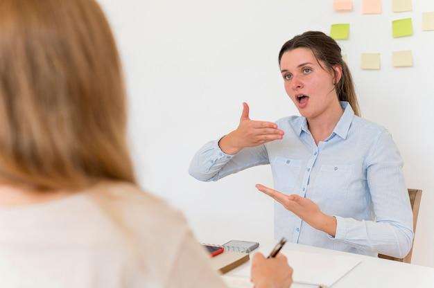 Frau, die jemand anderem die gebärdensprache beibringt