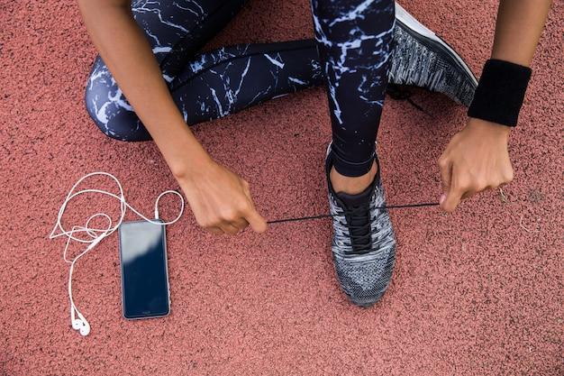 Frau, die joggingschuhe bindet