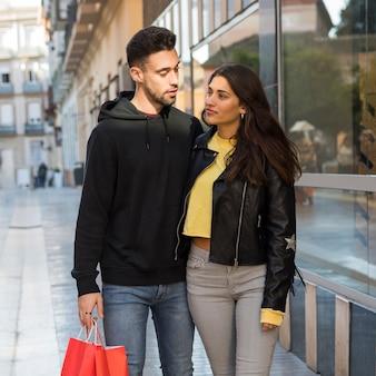 Frau, die jungen mann mit einkaufspaketen umarmt