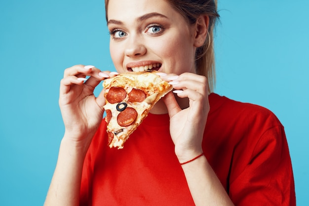 Frau, die junk-food auf einer farbigen oberfläche isst