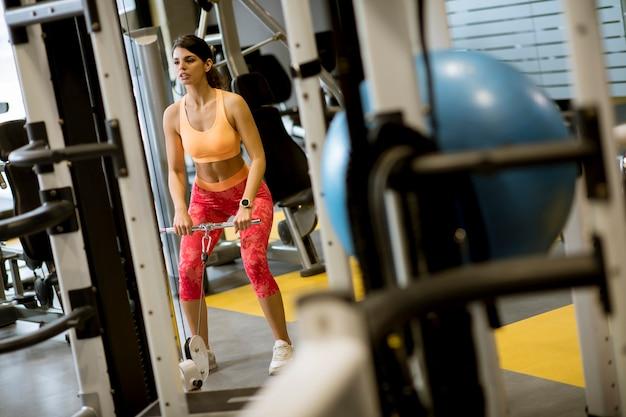 Frau, die kabel der geraden stange verwendet, um gewichte hochzuziehen, um bizeps in der turnhalle zu trainieren