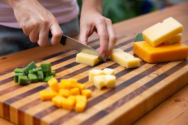 Frau, die käse auf würfel mit messer schneidet