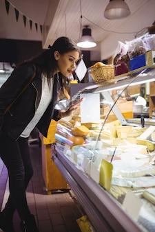 Frau, die käseanzeige betrachtet