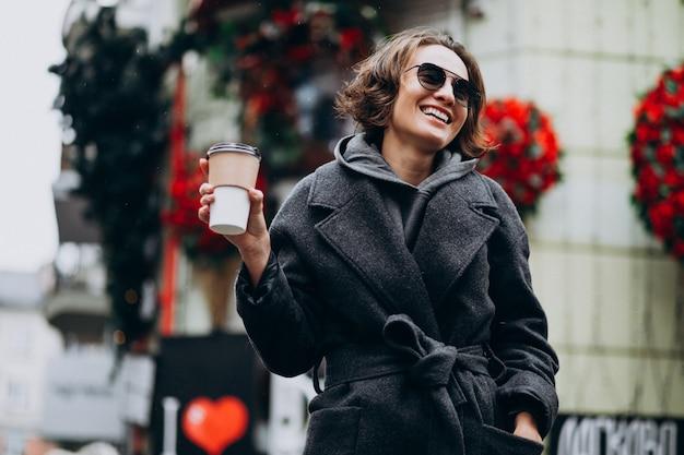 Frau, die kaffee außerhalb der straße trinkt