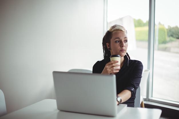 Frau, die kaffee bei der anwendung des laptops trinkt