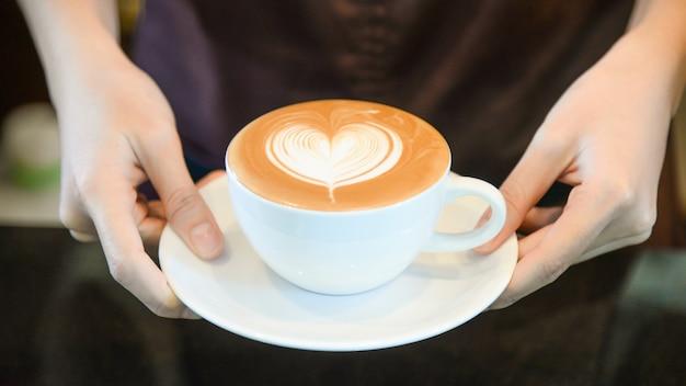 Frau, die kaffee beim stehen im kaffeehaus dient. konzentrieren sie sich auf latte art herdform tasse in weiblichen händen, während sie kaffee auf theke stellen