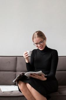Frau, die kaffee genießt und zeitschrift liest