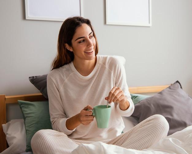 Frau, die kaffee im bett hat