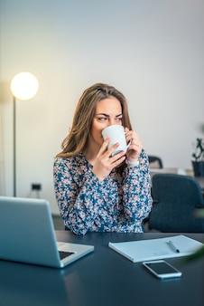 Frau, die kaffee im büro trinkend genießt.