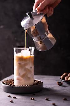 Frau, die kaffee in ein glas gießt