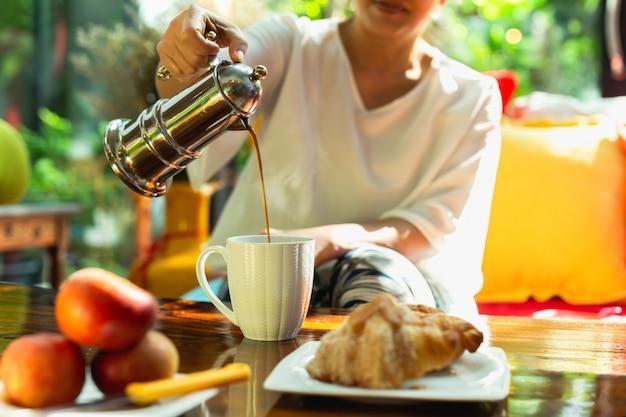 Frau, die kaffee in eine tasse von einer kaffeemaschine mit essen auf tisch gießt.