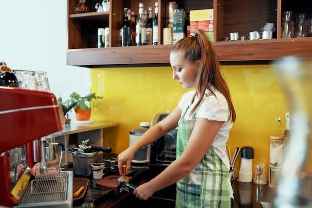 Frau, die kaffee mit stampfer zubereitet