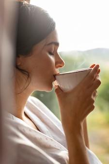 Frau, die kaffee nah oben trinkt