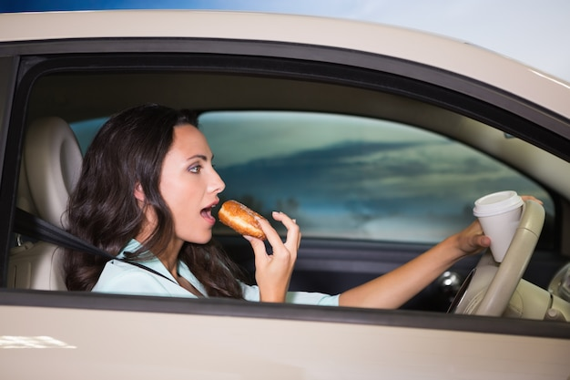 Frau, die kaffee trinkt und donna in ihrem auto isst