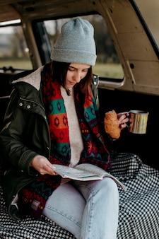 Frau, die kaffee trinkt und eine karte für ein neues ziel betrachtet