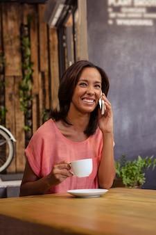 Frau, die kaffee trinkt und smartphone verwendet