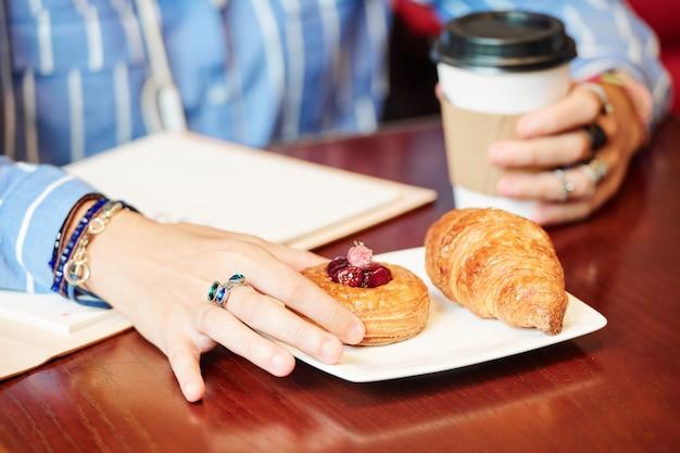 Frau, die kaffee und kirschgebäck hat