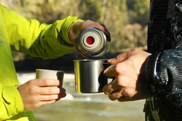 Frau, die kaffee von einer thermoskanne in eine tasse mann gießt