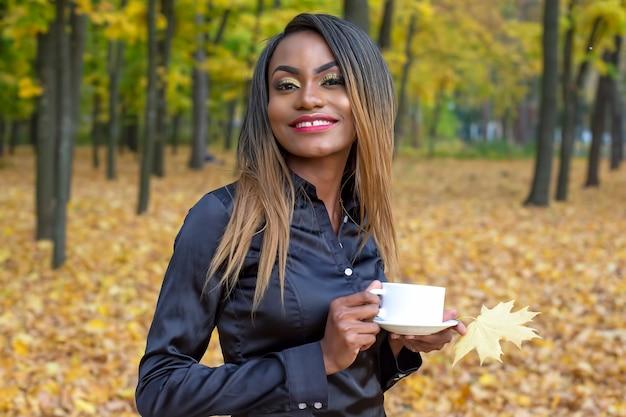 Frau, die kaffee von einer weißen tasse im park trinkt
