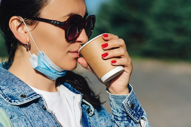 Frau, die kaffee zum mitnehmen trinkt. profil des hübschen mädchens mit sonnenbrille.