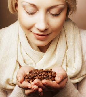 Frau, die kaffeebohnen hält.