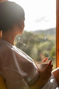 Frau, die kaffeeschale mittleren schuss hält