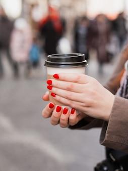Frau, die kaffeetasse auf der verschwommenen straße hält. sonniger frühlingsnachmittag. rote maniküre