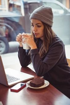 Frau, die kaffeetasse hält und laptop im restaurant betrachtet