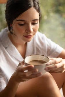 Frau, die kaffeetasse hält