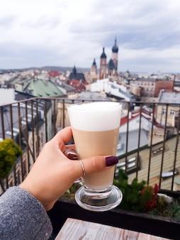 Frau, die kaffeetasse im café auf einem dach mit ansicht zu st mary church krakow hält