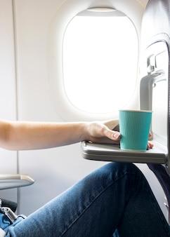 Frau, die kaffeetasse im flugzeug hält