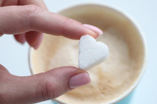 Frau, die kaffeezuckerwürfel in form der herznahaufnahme setzt