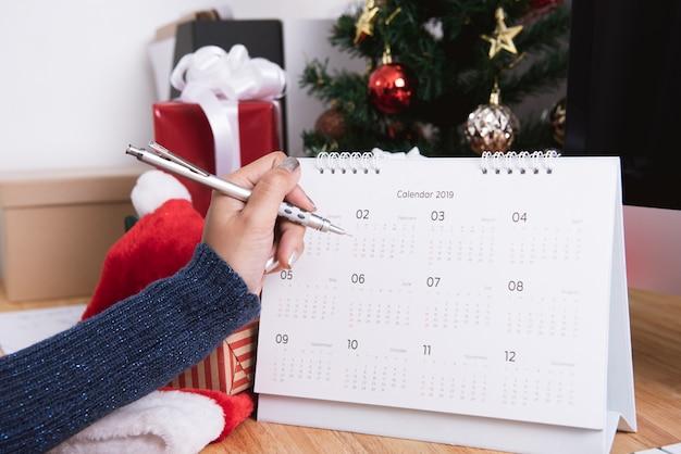 Frau, die kalenderplaner in den weihnachtsfeiertagen im büro mit weihnachtsdekoration schreibt