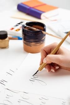 Frau, die kalligraphie auf postkarten schreibt