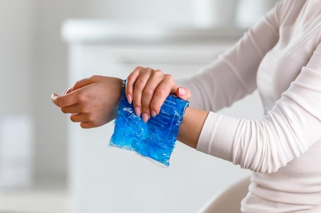 Frau, die kalte kompresse auf ein schmerzhaftes handgelenk anwendet, verursacht durch längere arbeit am computer, laptop, kopierraum