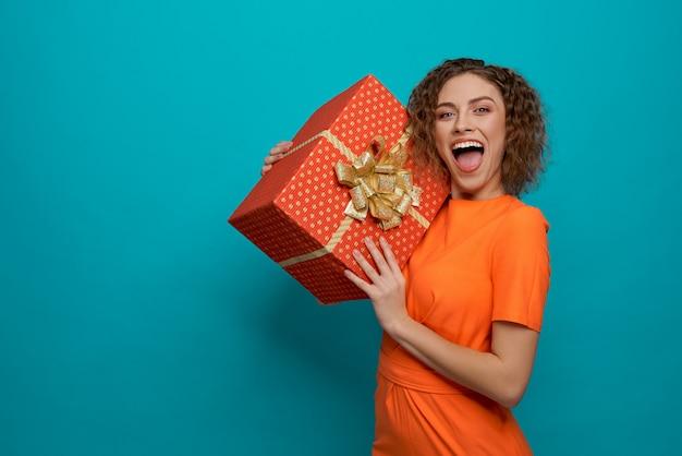 Frau, die kamera betrachtet und beim halten des geschenkes schreit