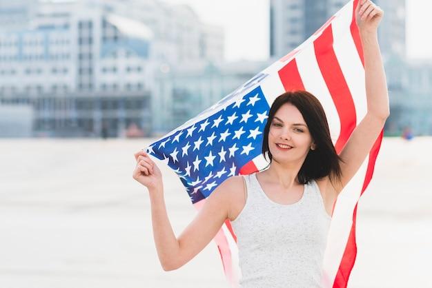 Frau, die kamera betrachtet und breite amerikanische flagge wellenartig bewegt