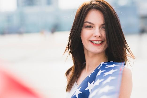 Frau, die kamera betrachtet und mit sternen der amerikanischen flagge wellenartig bewegend lächelt