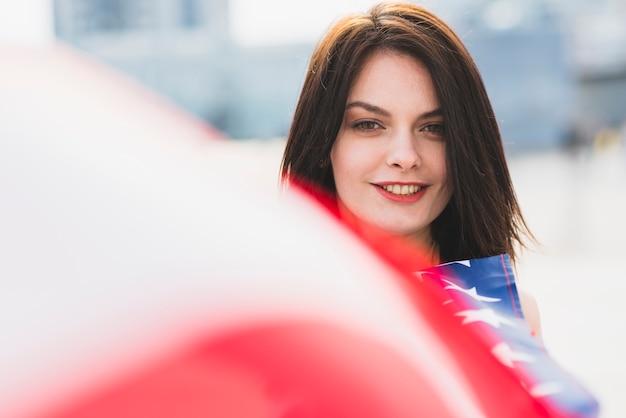 Frau, die kamera betrachtet und wellenartig bewegende amerikanische flagge lächelt