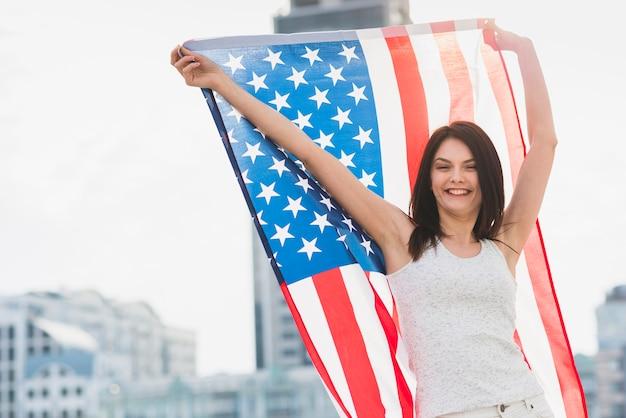 Frau, die kamera betrachtet und wellenartig bewegende breite amerikanische flagge lacht