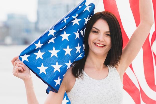Frau, die kamera betrachtet und wellenartig bewegende breite amerikanische flagge lächelt
