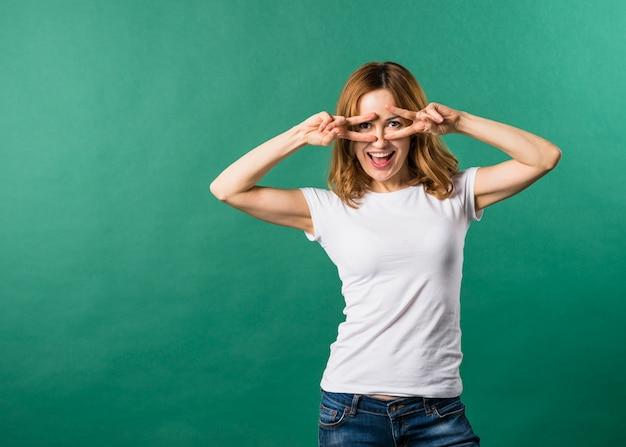 Frau, die kamera durch finger in der sieggeste gegen grünen hintergrund betrachtet