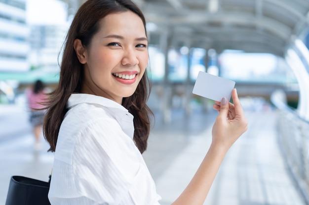 Frau, die kamera mit dem lächeln betrachtet und weiße karte an der außenseite hält