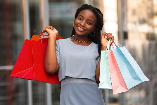Frau, die kamera mit einkaufstaschen betrachtet