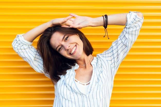 Frau, die kamera mit gelbem hintergrund betrachtet